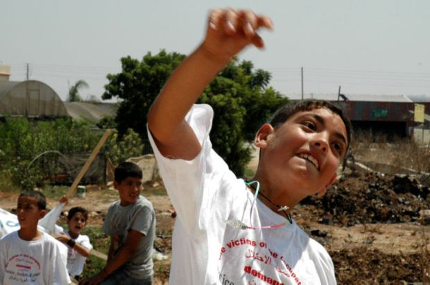 En palestinsk gutt kaster stein på den israelske hæren. Bildet: Justin McIntosh